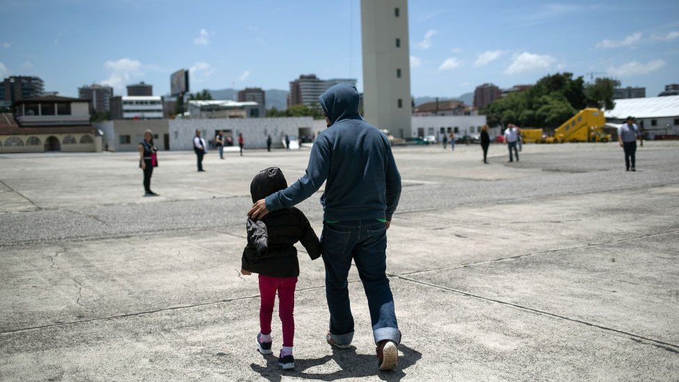 A father walking with his daughter at the airport in Brownsville, TX, towards a deportation flight