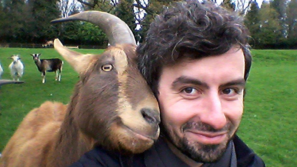 Рогата коза разом із усміхненим науковцем