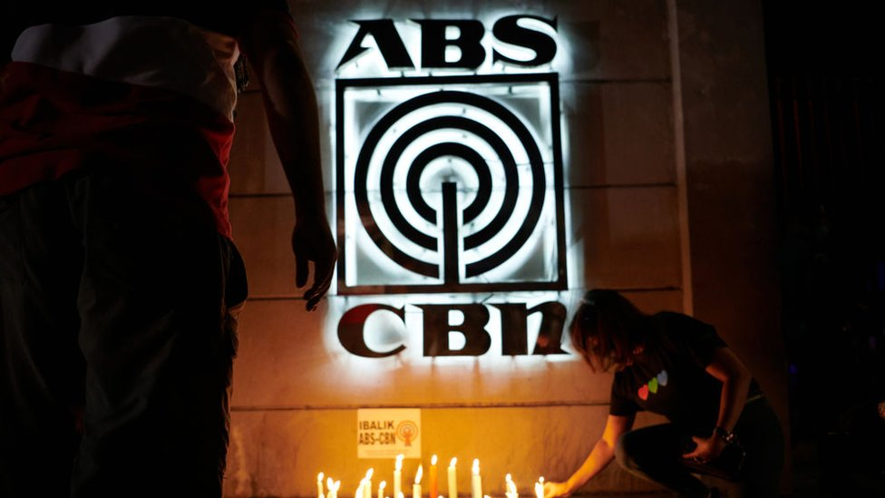 : Employees and supporters of ABS-CBN light candles in front of its main studio to show support