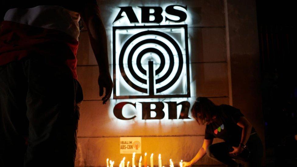 : Karyawan dan pendukung lampu lilin ABS-CBN di depan studio utamanya untuk menunjukkan dukungan