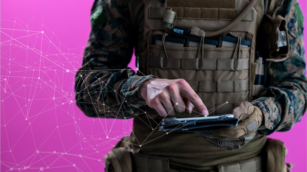 A photo illustration shows a man in combat fatigues tapping on a tablet, from which flows an abstract representation of data into the pink background