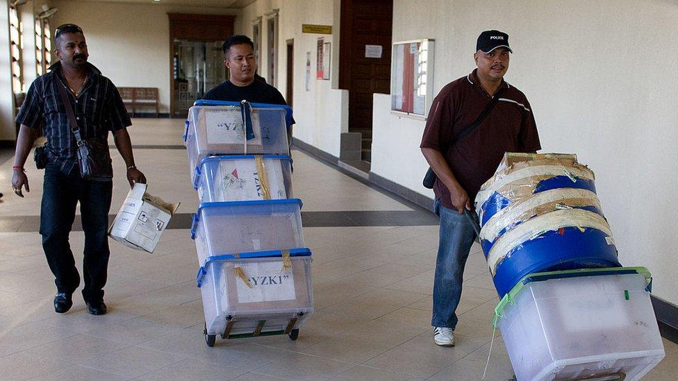 Funcionarios transportan pruebas del caso de narcotráfico en el que estuvieron involucrados los tres mexicanos.
