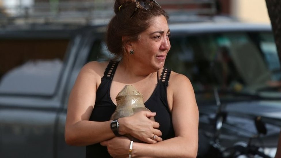 A relative carries the ashes of a victim of the Boeing 737 plane crash as she leaves a funeral parlour in Havana, Cuba, May 21, 2018.