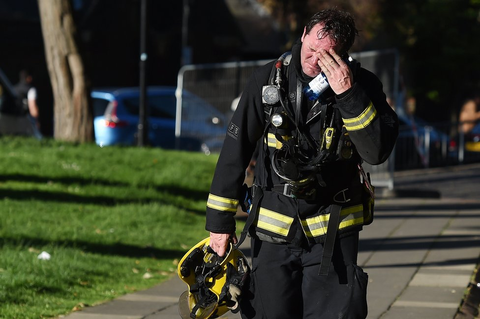 A firemen reacts after battling the huge fire at the Grenfell Tower