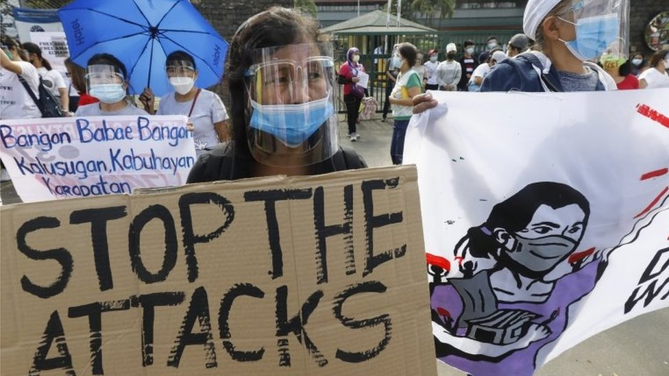 A protester holds a sign during a rally marking International Women's Day in Quezon City, Metro Manila, Philippines, 8 March 2021