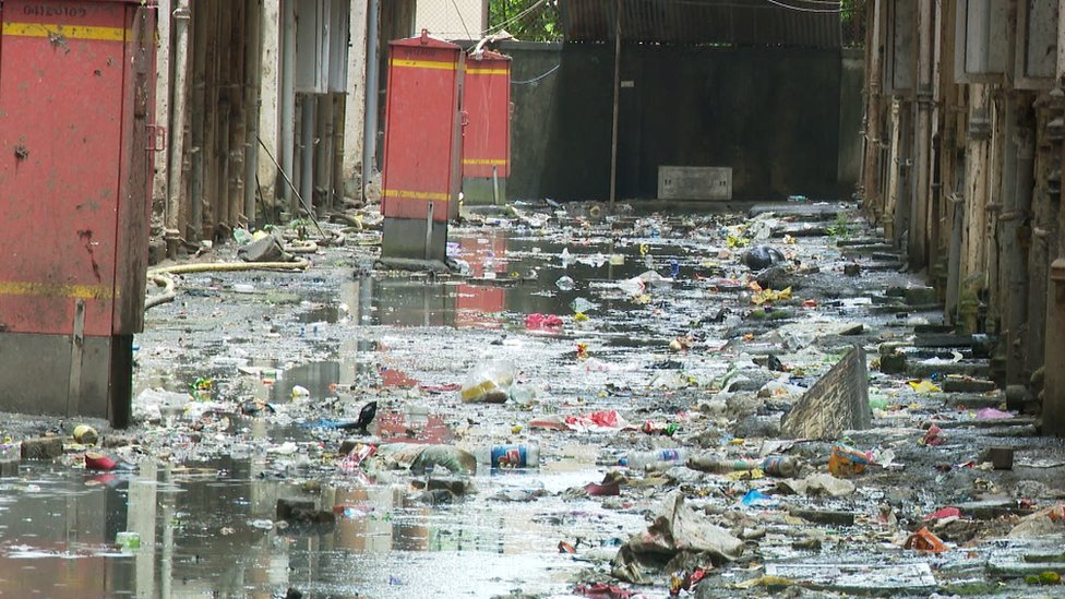 An overflowing sewer between homes in Mahul