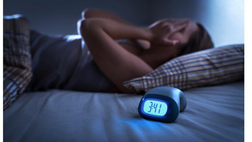 Mujer en la cama con insomnio.