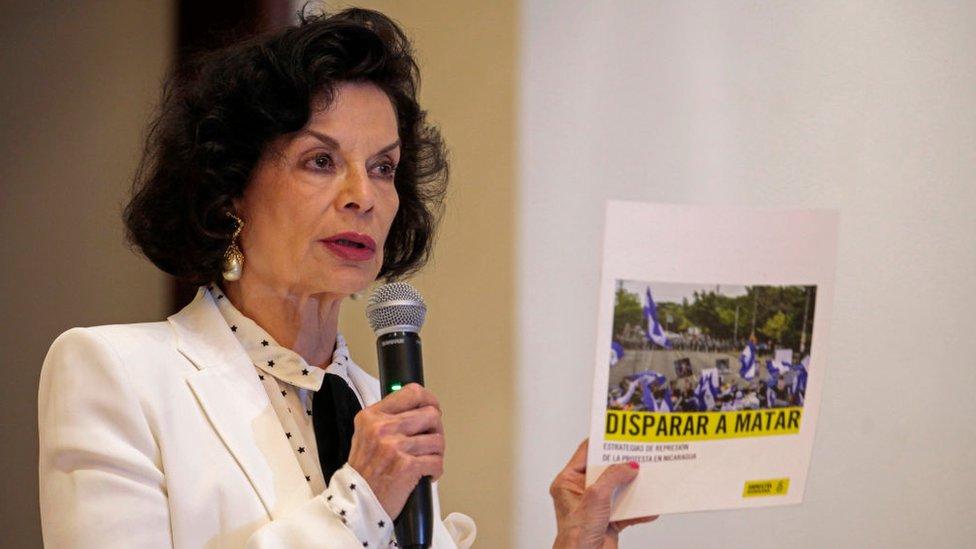 Mujer señalando informe de Amnistía Internacional