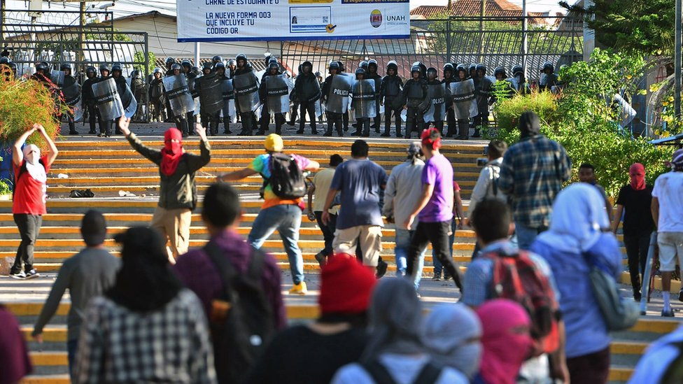 Students of the National Autonomous University of Honduras confront riot police during a protest