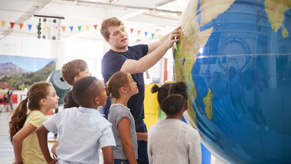 Maestro con niños señalando un globo terráqueo.
