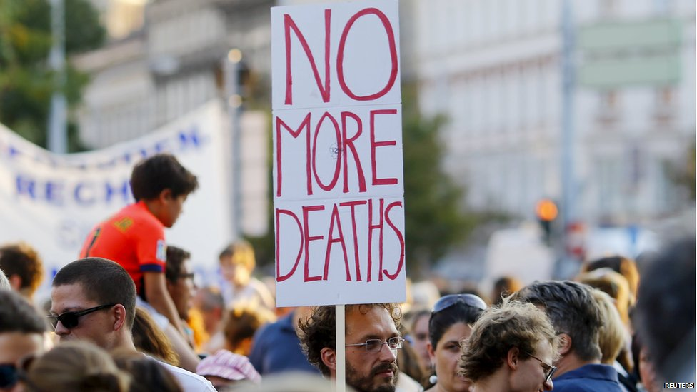 "A man holds up a sign reading ""no more deaths"" at a rally in Vienna"