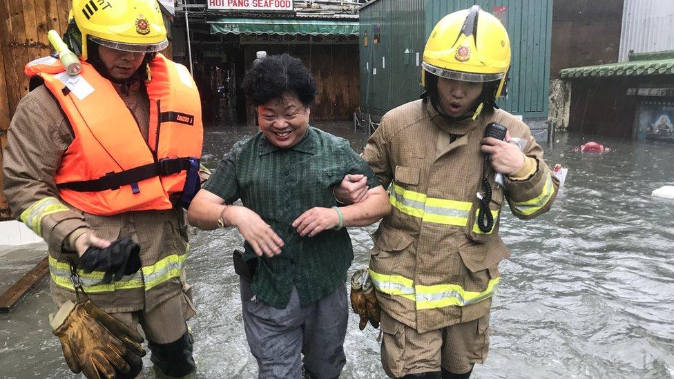 山竹颱風吹襲期間香港九龍鯉魚門一位女村民由消防員攙扶離開海水倒灌區域(16/9/2018)
