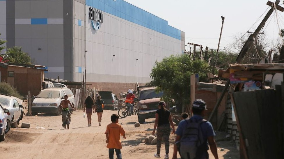 People walk near an informal settlement next the new Amazon fulfilment centre, which is under construction at the RMSG Alamar Industrial Park, in Tijuana, Mexico September 7, 2021.
