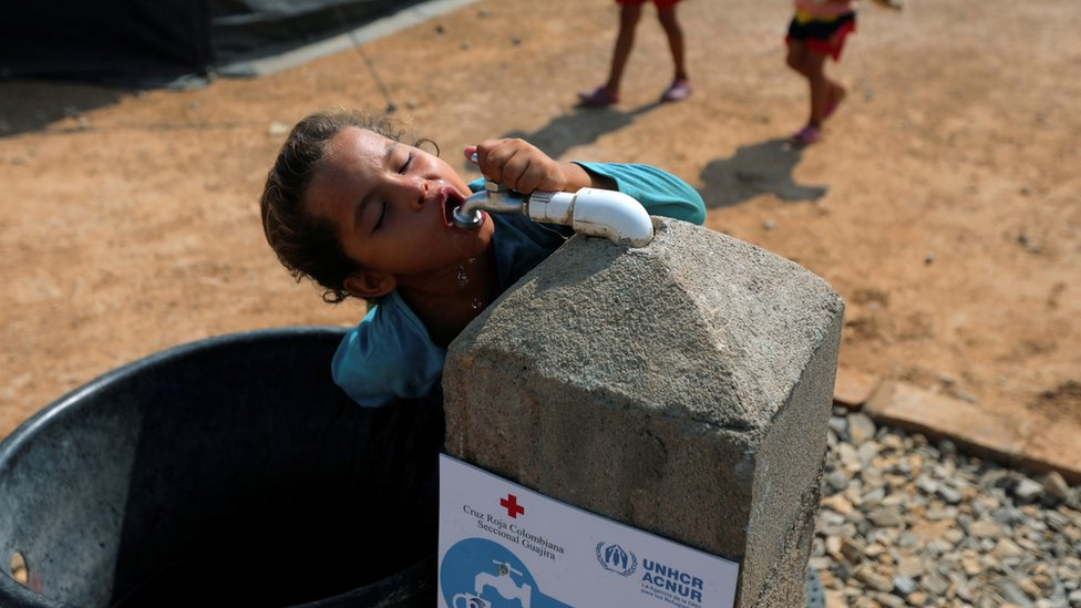 A Venezuelan migrant girl drinks water from the tap, in a camp run by the UN refugee agency UNHCR in Maicao, Colombia May 7, 2019. Picture taken May 7, 2019.