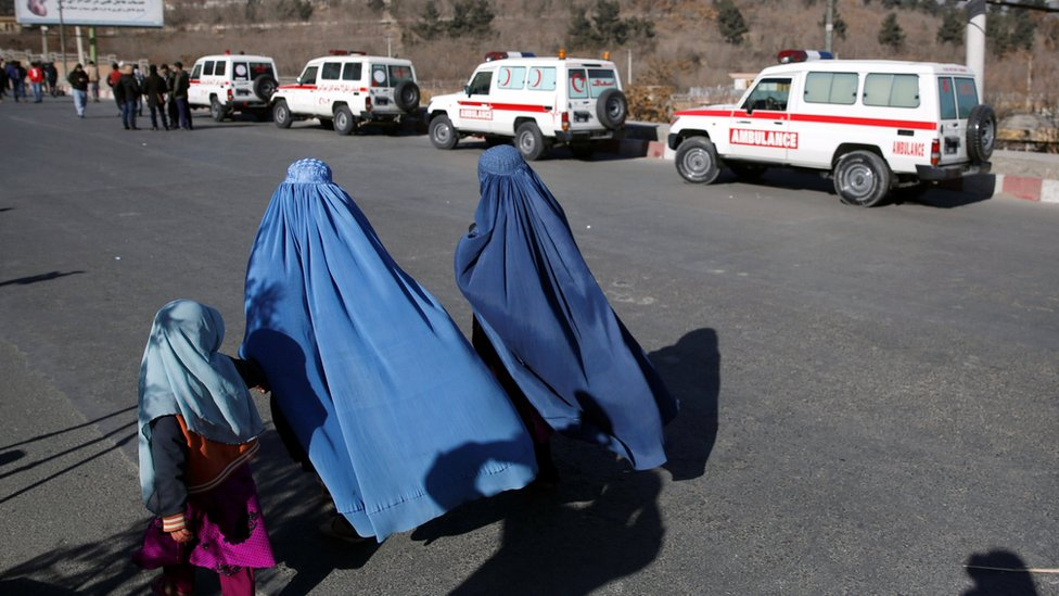 Afghan women walk past ambulances at the scene of the hotel attack in Kabul on 21 January 2018