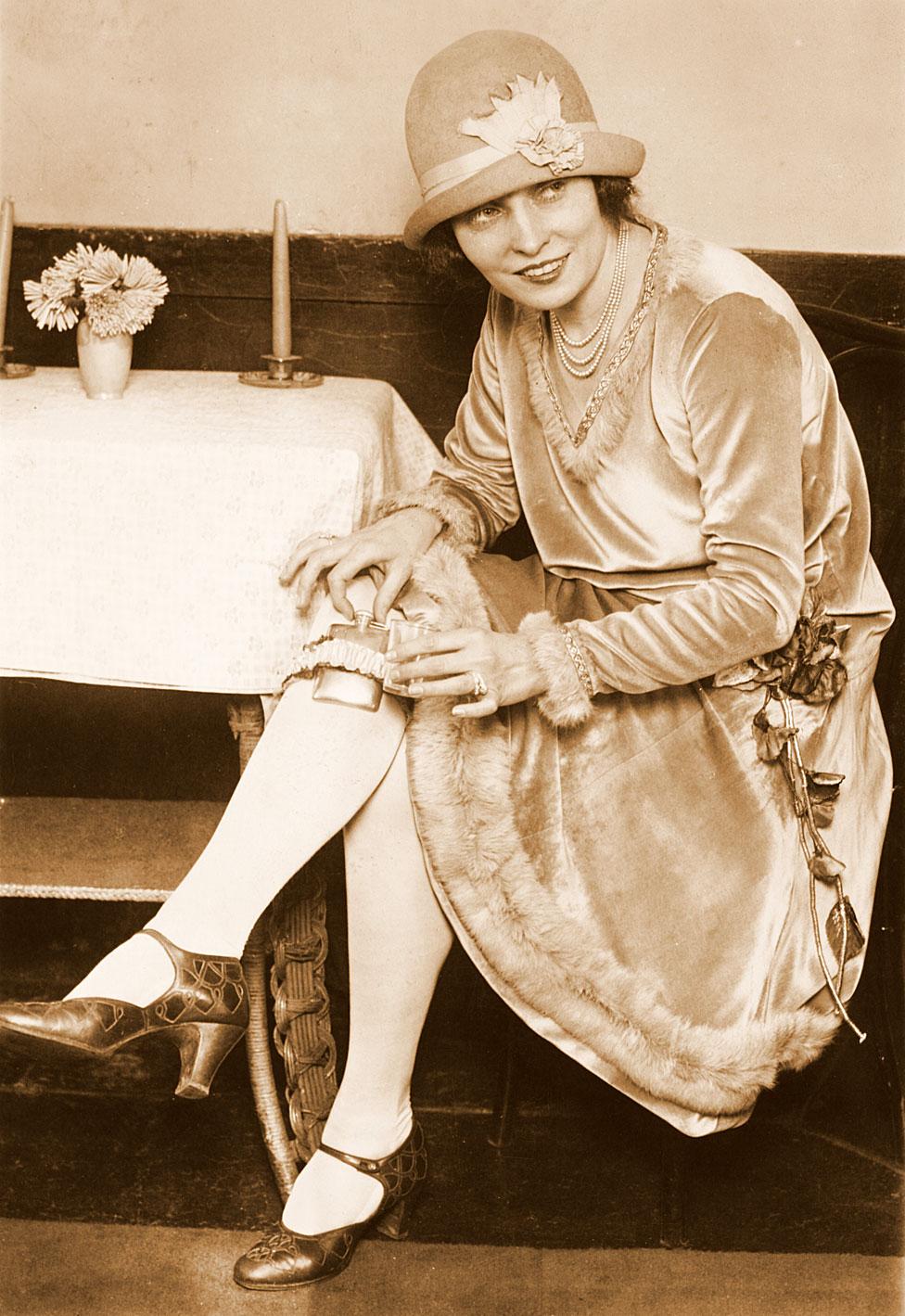 chica de Washington DC que en 1926 sonríe mostrando dónde escondía su whisky.