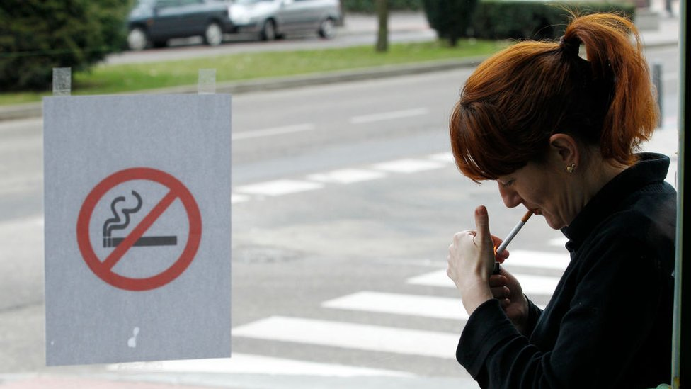 Image shows woman smoking outside a bar in Spain