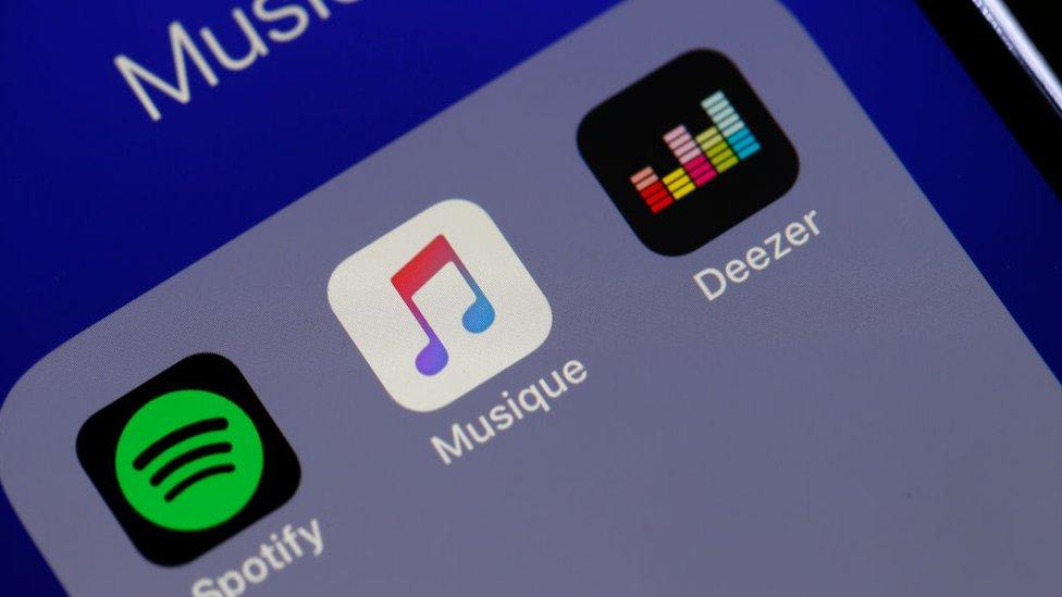 Pantalla de celular con algunas aplicaciones de música: Spotify, Apple Music y Deezer.