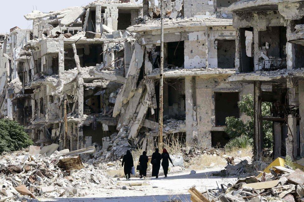 Women walk in between destroyed buildings in the Jouret al-Shiah neighbourhood of the central Syrian city of Homs (19 September 2016)