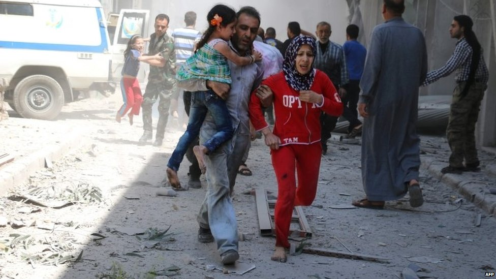 A Syrian family runs for cover following a reported air strike Aleppo