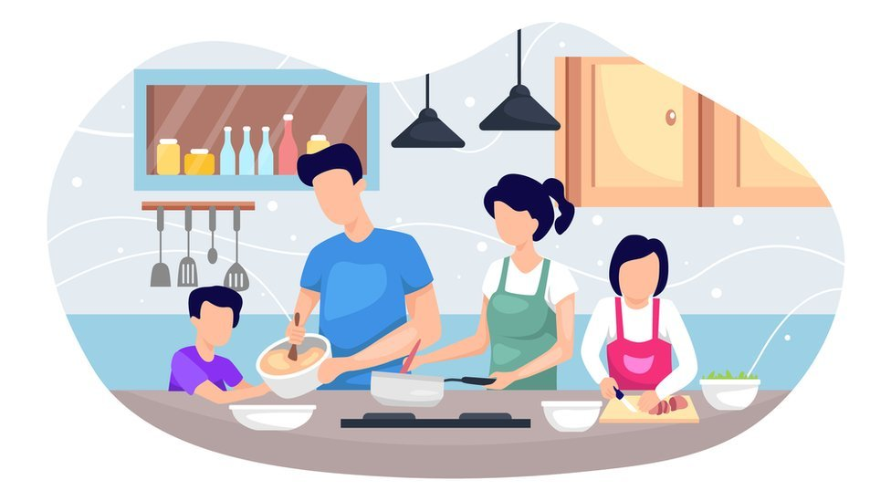 Family cooking a meal together with young children