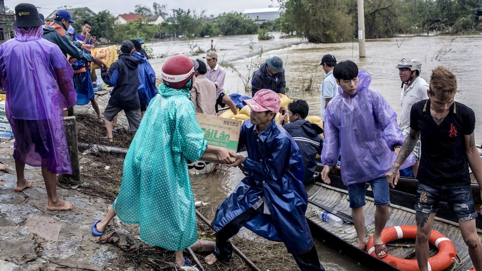 Local residents and volunteers deliver aid packages to residents affected by heavy flood in Quang An Commune, Thua Thien Hue, Vietnam, 20 October 2020