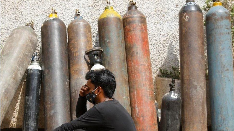 Seorang pria menunggu di luar pabrik untuk mengisi ulang tabung oksigen di New Delhi, India, (28/04).