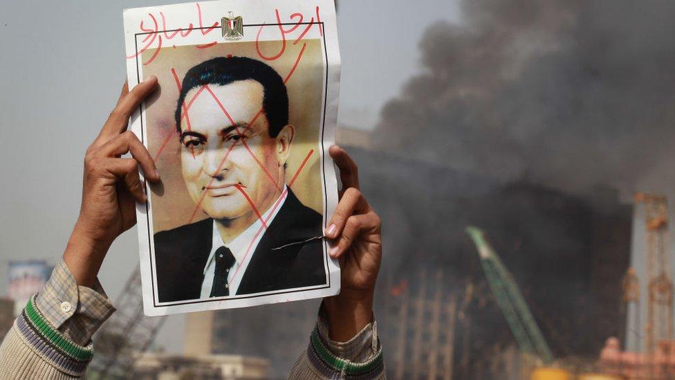 شخص يحمل صورة لمبارك وكتب عليها يدعوه للرحيل عن السلطة