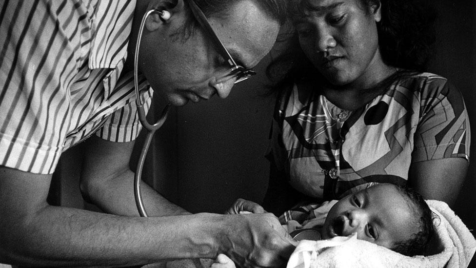Doctor examinando un bebé mientras la madre observa