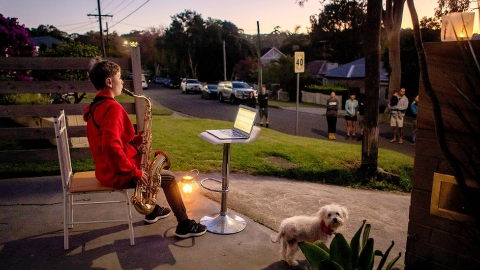 Jude Fell, aged 10, plays The Last Post on a saxophone from his driveway at dawn in Sydney on April 25, 2020