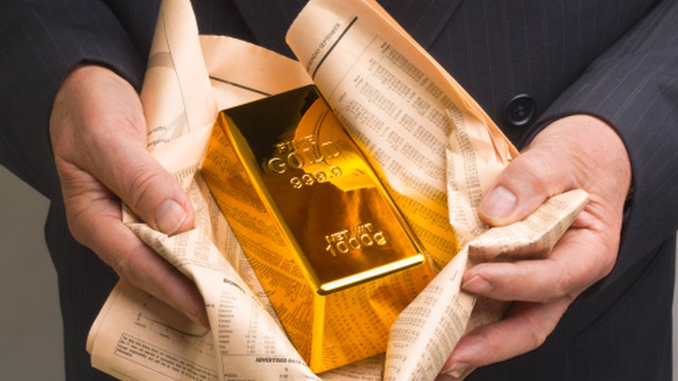 A gold bar wrapped in newspaper