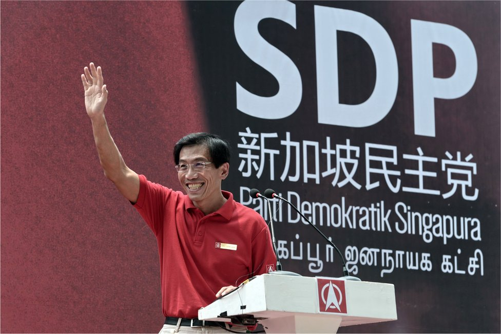 """Chee Soon Juan, the secretary-general of the opposition Singapore Democratic Party (SDP), waves to a lunch time crowd at a rally in the financial district of Raffles Place ahead of Singapore""""s September 11 election, on 7 September 2015."""