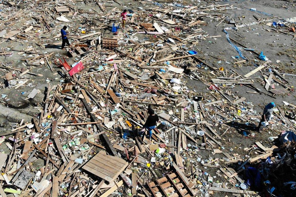 Overhead view of people looking through debris in Palu