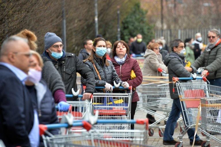 Milano'daki bir süpermarket kuyruğunda bekleyenler