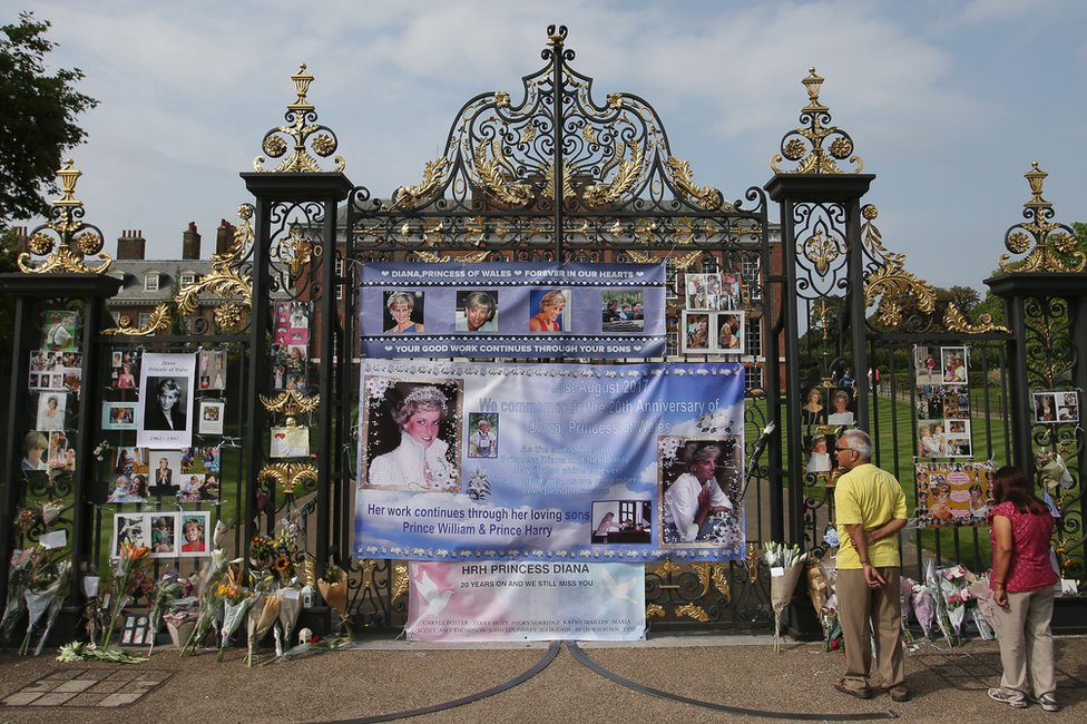 Visitors look at photographs of Diana, Princess of Wales, and floral tributes left outside Kensington Palace in Central London on 29 August, 2017