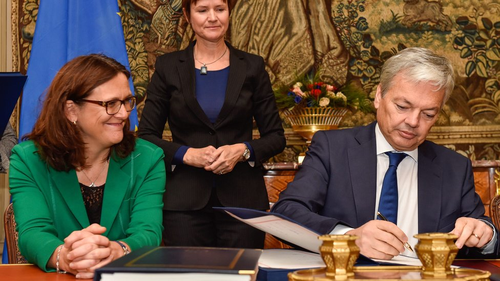 Belgian Foreign Minister Didier Reynders signs Belgian agreement on Ceta in presence of EU Trade commissioner Cecilia Malmstrom (L) - 29 October