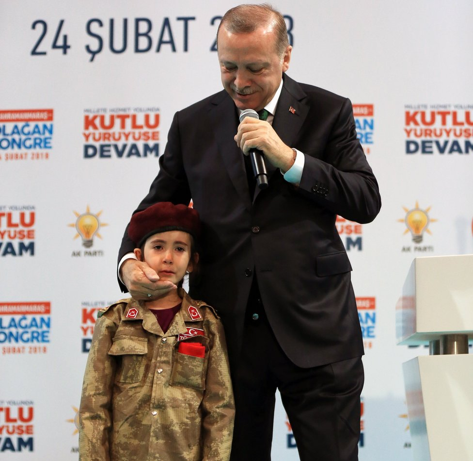 Turkish President Recep Tayyip Erdogan speaks alongside a girl dressed as a Turkish soldier