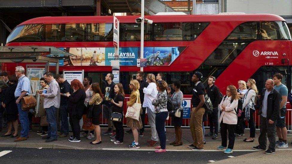 Commuters wait for London bus