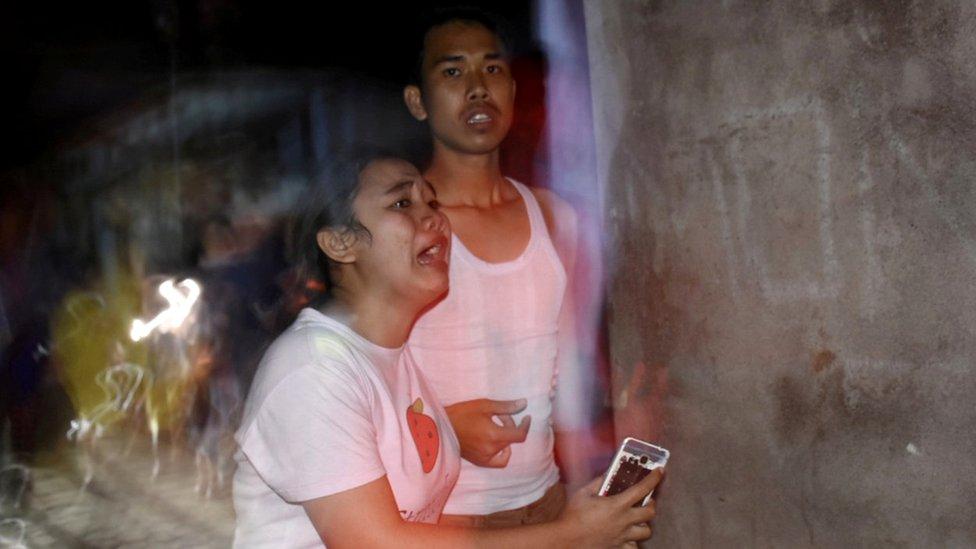 People react following an earthquake in Ampenan district, Mataram, Lombok,