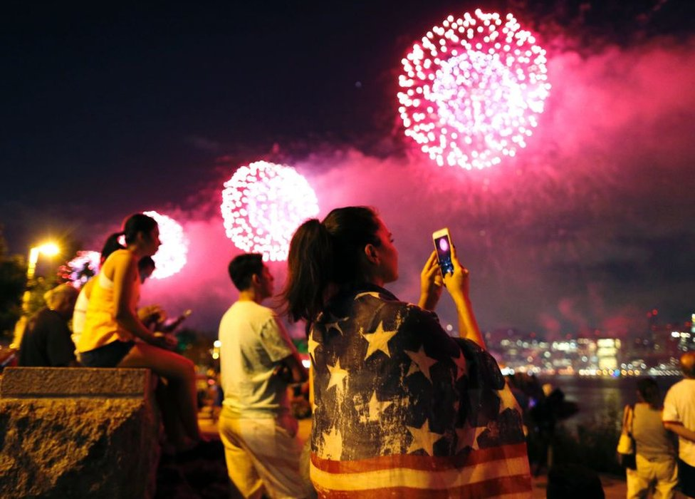 Varias personas observan los fuegos artificiales.