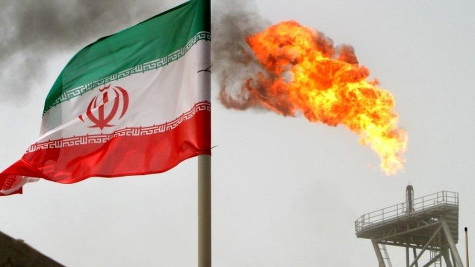 Bandera iraní y plataforma petrolera.