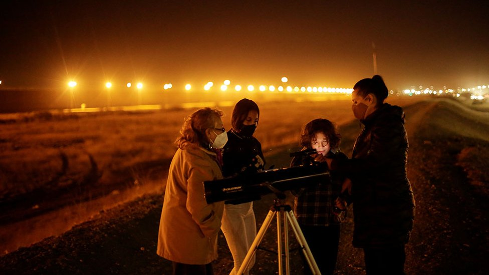 A family with a telescope in Ciudad Juarez, Mexico