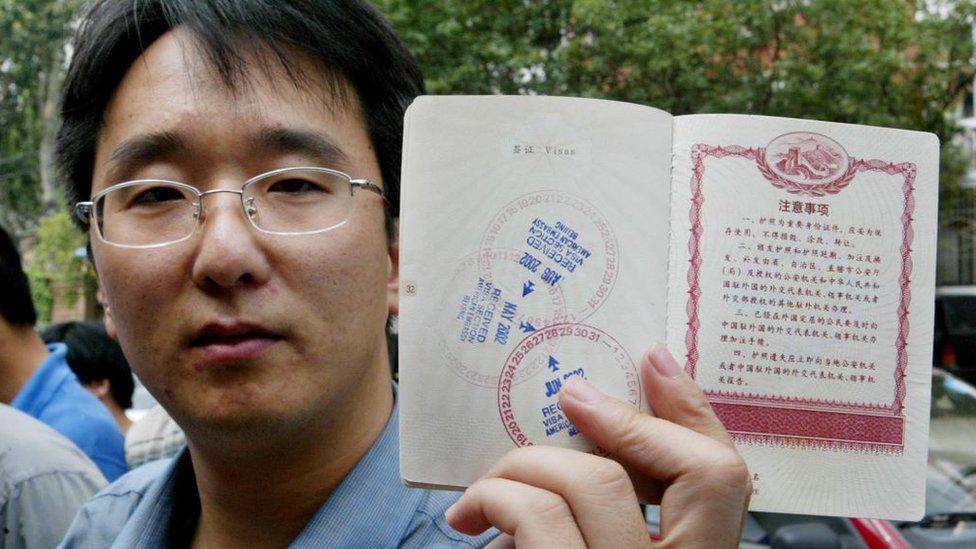 Hombre chino mostrando su pasaporte