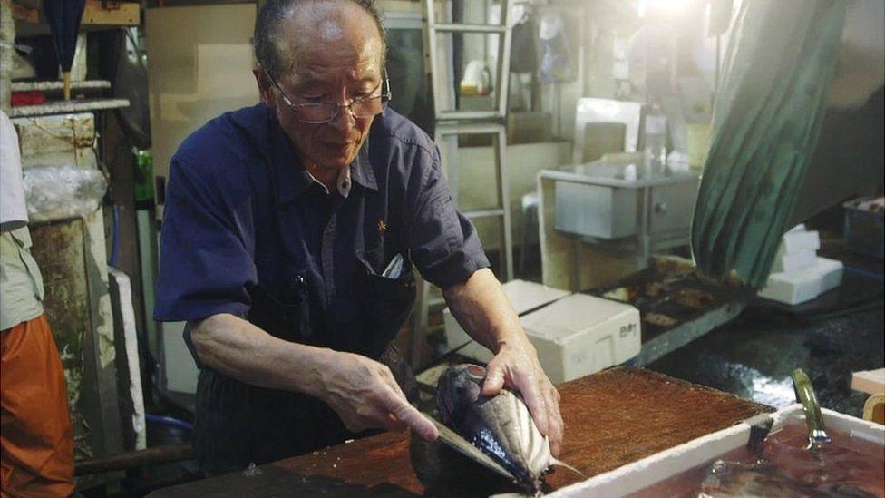 A fishmonger cuts open a fish