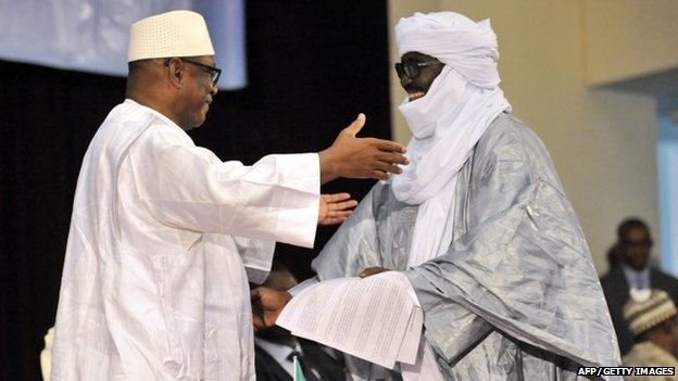 """Mali""""s President Ibrahim Boubacar Keita (L) embrasses Mahamadou Djery Maiga (R), the vice-president and spokesman of the Transitional Council of the State of Azawad, following the signing of the ammended version of the Algerian Accord on June 20, 2015 in Bamako."""