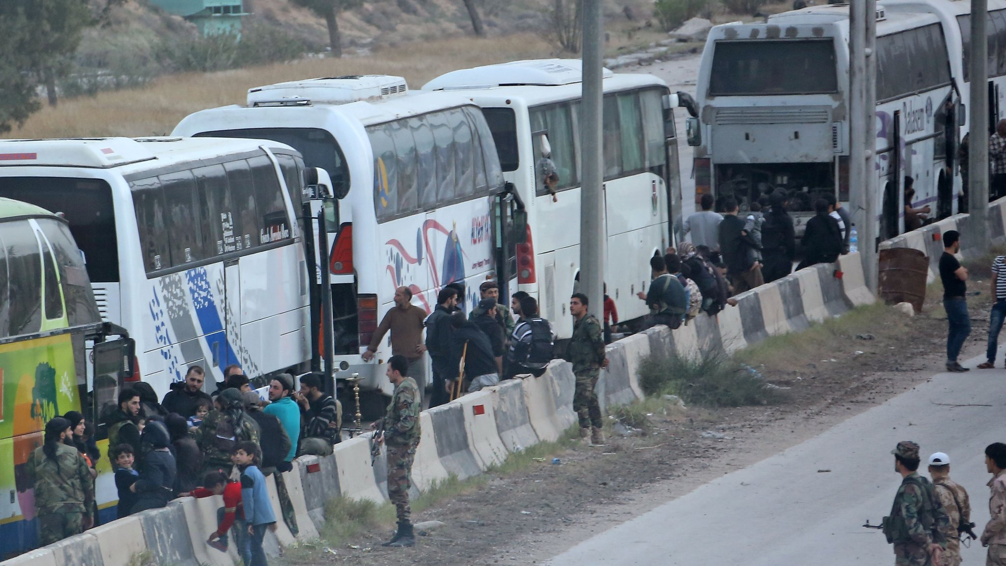 Buses wait to transport Syrian rebel fighters and their families from the town of Harasta, in the Eastern Ghouta, to Idlib province (22 March 2018)