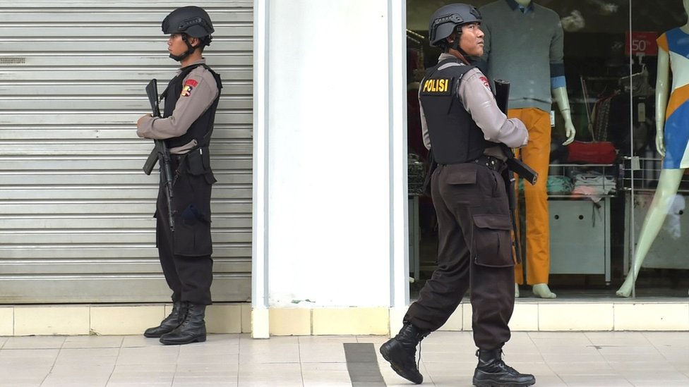 Two Indonesian anti-terror policemen stand guard next to the Starbuck cafe after several blasts and shootings in Jakarta (14 January 2016)