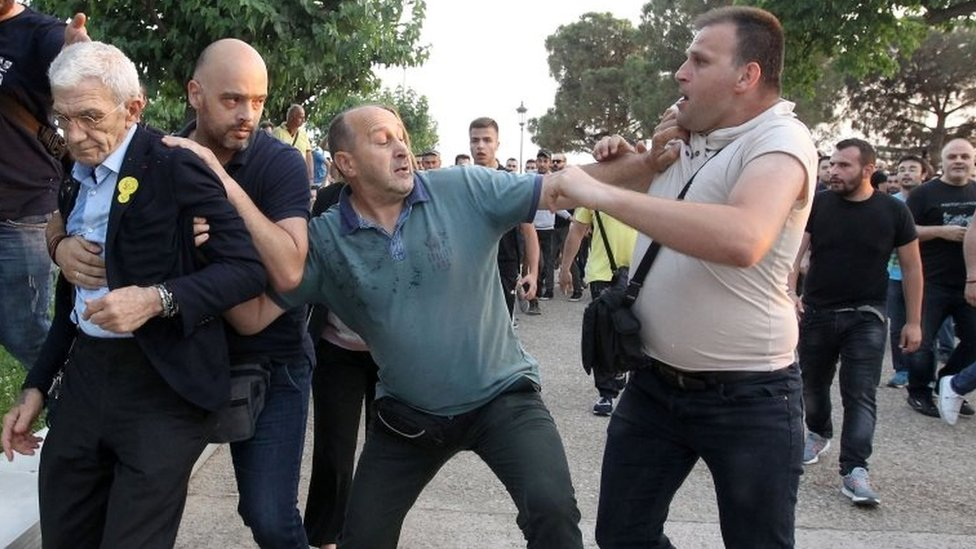 Mayor of Thessaloniki, Yiannis Boutaris (L), is protected from an attack by a group of nationalists during Remembrance Day on 19 May 2018.