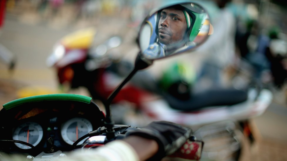 Motorcycle taxi driver Jean Claude Bigirimana, 31, waits for a customer at the Nyabugogo neighborhood bus park April 9, 2014 in Kigali, Rwanda.