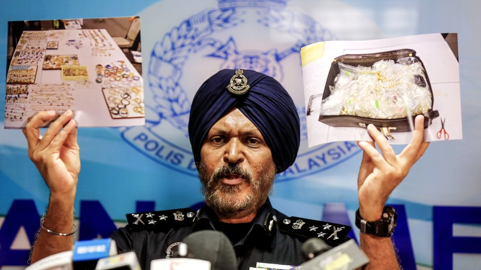 Police officer displays photos of items from a raid during a news conference in Kuala Lumpur, Malaysia June 27, 2018.